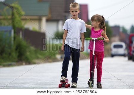 Cute Young Blond Children, Brother And Sister, Girl In Pink Clothing On Scooter And Handsome Boy On