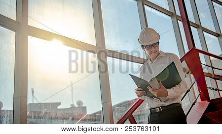 Young Asian Male Engineer Or Architect Holding Files Wearing Protective Safety Helmet On Red Stair A
