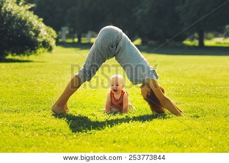 Woman Doing Yoga With Baby In Nature