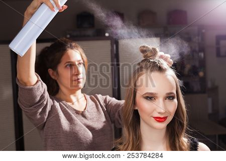 hairdresser fixing a coiffure with an unusual bun of a young beautiful girl using a hair spray in a beauty salon. concept of professional stylist studying poster
