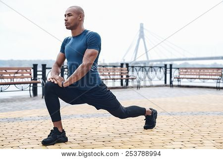 Young Male Jogger Athlete Training And Doing Workout Outdoors In