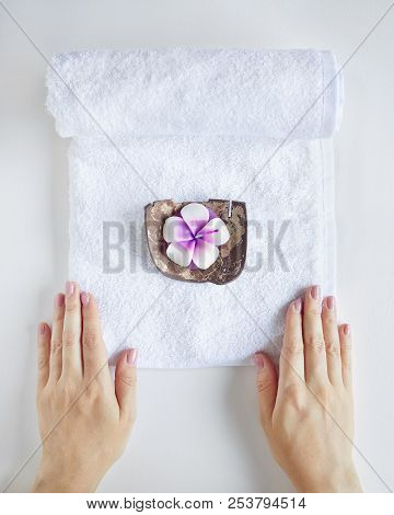 Spa And Treatment. Woman Holding White Towel With Violet Candle On White Plain Background