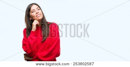 Young beautiful hispanic wearing red sweater with hand on chin thinking about question, pensive expression. Smiling with thoughtful face. Doubt concept.