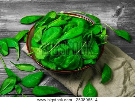 Fresh Green Leaves Mini Spinach In Ceramic Bowl. Spinach Leaves On The Gray Wooden Rustic Background