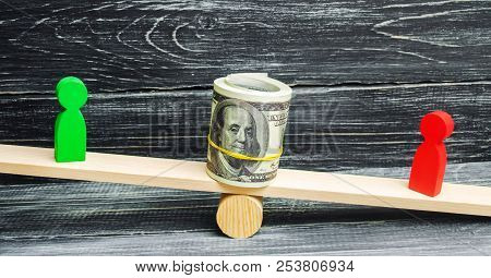 Wooden Figures Of People On Scales And Dollars Between Them. A Dispute Between Two Businessmen. Tria