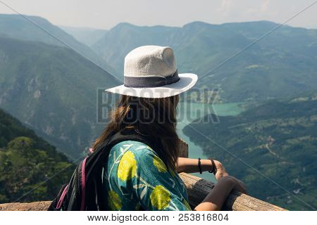 Girl Relaxing On A Beautiful Mountain View. Traveler Standing On Mountain Rock Enjoying Beautiful Mo
