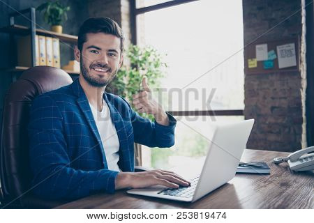 Portrait of attractive handsome young brunet smiling executive worker man, sitting in office workstation workplace, using laptop, showing thumb up poster