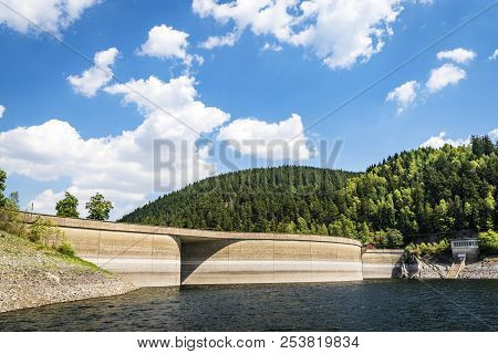 River With A Dam Surrounded By Hills And Pine Trees Under A Blue Sky