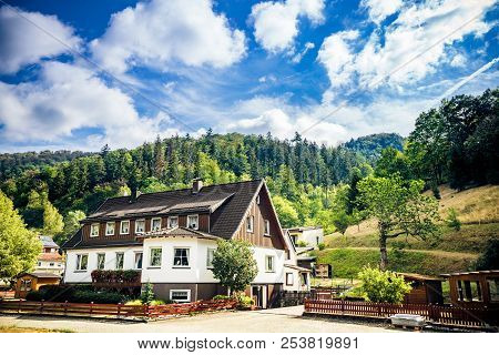 Idyllic House In The German Alps With Green Forest In The Background Under A Blue Sky In The Summer