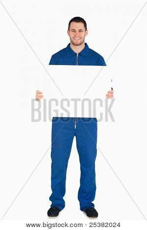 Smiling young mechanic in boiler suit holding a banner against a white background