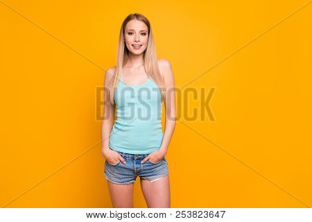 Charming Blond Girl Looking At Camera Keeps Her Hands In Pockets Isolated On Shine Yellow Background