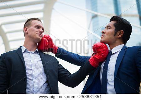 Caucasian Businessman Wear Black Suit And Asian Businessman Man Wear Blue Suit With Red Boxing Glove