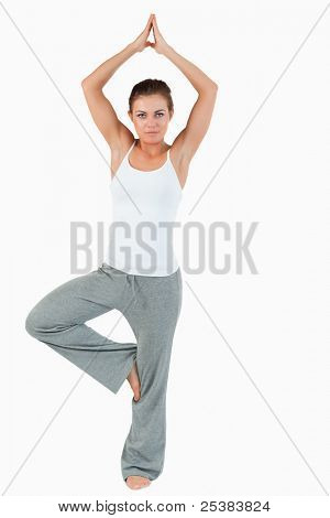Portrait of a woman in the Vrksasana position against a white background