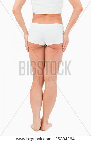 Portrait of a woman with the hands on her thigh against a white background