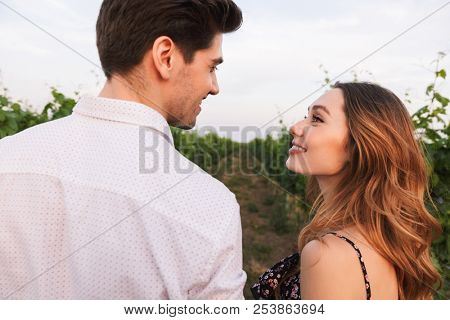 Loving young couple man and woman dating while walking outdoor together through vineyard on summer day