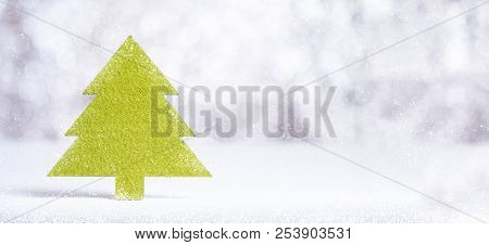 Close Up Merry Christmas Word On Green Christmas Tree With Sparkling Red Star With Snow Fall On Whit