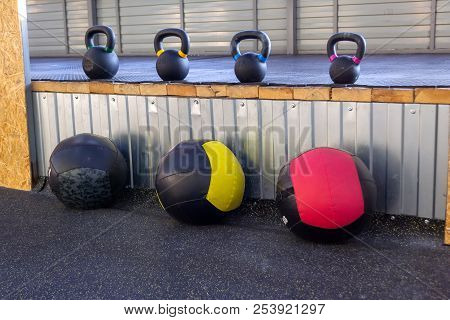 Iron Dumbbells Of Different Weights With Multi-colored Handles Stand In The Gym On A Rubber Mat. Med