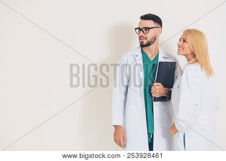 Confident Surgical Doctor Holds Document Clipboard While Standing With Another Doctor On White Backg