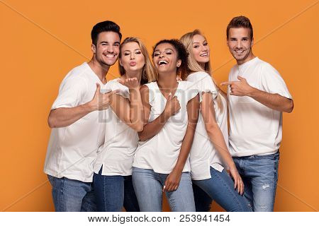 Group Of Beautiful Friends Posing Together In Studio.