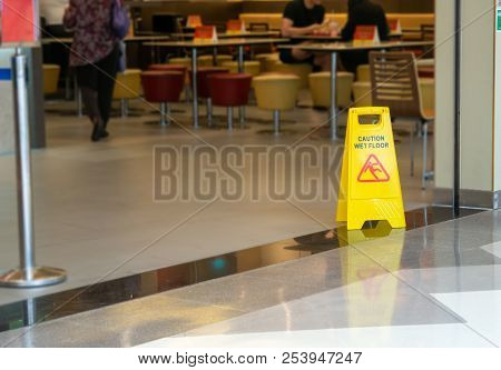 Yellow Plastic Cone With Sign Showing Warning Of Wet Floor In Restaurant In Department Store