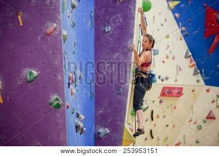 Photo of young athlete in training on purple wall for rock climbing