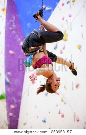 Photo of young athlete hanging upside down on wall for rock climbing