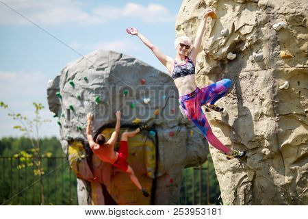 Photo of sports man and smiling woman in sunglasses climbing on boulders for rock climbing against blue sky with clouds