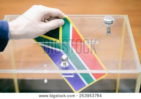 Man inserting Flag of South Africa into ballot box, voting and elections in South Africa. poster