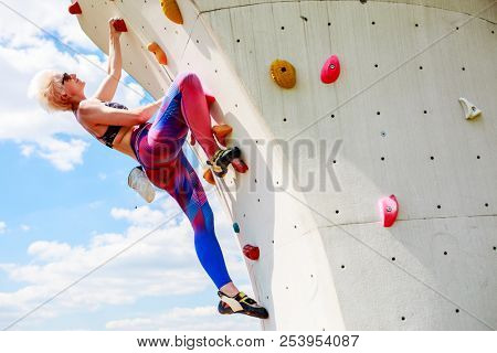 Photo of young girl on training at climbing wall