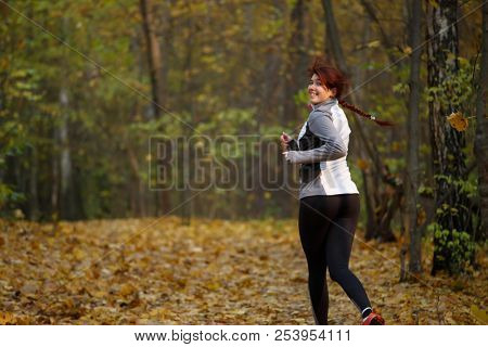 Image of happy girl in sports clothes on run in autumn