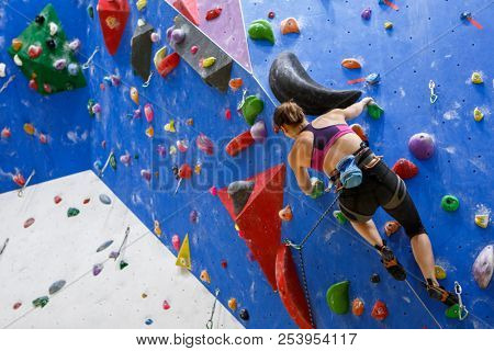 Photo of sports girl from back with bag for talc climbing on wall