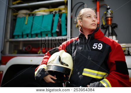 Photo of young woman firefighter looking to side next to fire engine