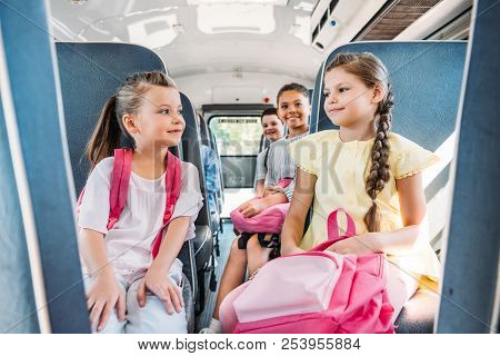 Group Of Happy Pupils Riding On School Bus During School Excursion
