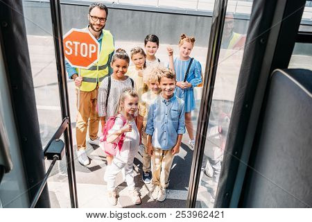 View From School Bus At Group Of Happy Scholars With Traffic Guard Looking At Camera