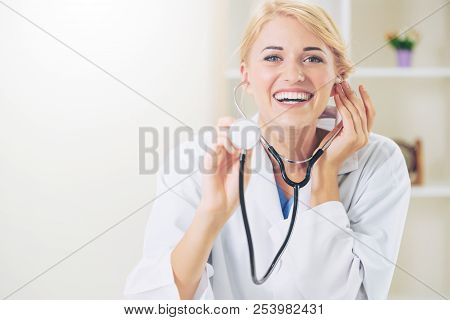 Young Female Doctor Pointing Stethoscope At Blank Space. Selective Focus At Doctors Face. Medical He