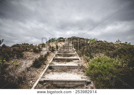 Wooden Stairs Going To The Top Of A Hill In Dramatic Cloudy Weather