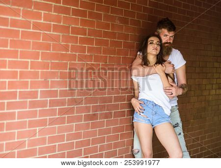He Will Never Let Her Go. Couple In Love Hugs Brick Wall Background. Couple Find Place To Be Alone.
