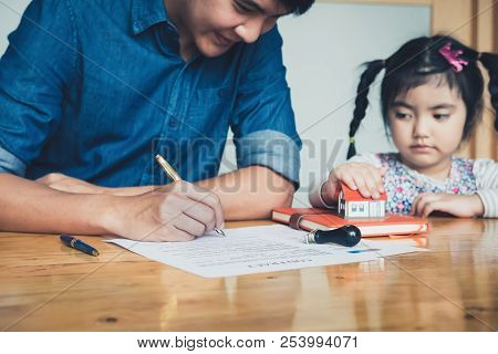 Family Hands Holding Small House Between Signing Contract,concept For Real Estate,insurance And Safe