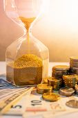 Sand running through the shape of hourglass with banknotes and coins stack of international currency on table. Time investment. retirement saving. Urgency countdown timer for business deadline concept poster