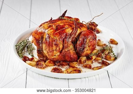 Roast Chicken With Forty Cloves Of Garlic, 40-clove Chicken On A White Platter, On A Wooden Table, F