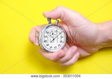 Mechanical Stopwatch In A Man's Hand On A Yellow Background.