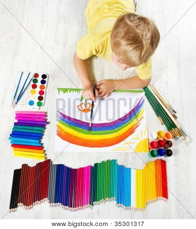 Child Painting Picture With Brush In Album Using A Lot Of Painting Tools. Top View.