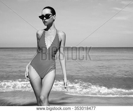 Beautiful sexy lady on tropical beach. Fashionable woman with slim perfect figure walking in front of blue sea. Model pose in swimwear and modern sunglasses. Relax portrait of young sunbathing beauty