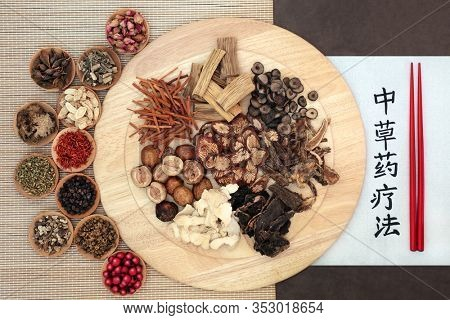 Traditional Chinese herbs used in herbal medicine on a wooden board, bamboo & lotka paper background with chopsticks & calligraphy script. Translation reads as traditional Chinese herbal therapy.