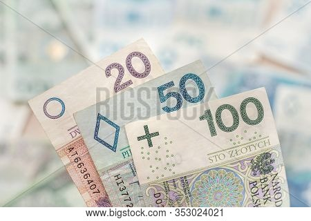 Banknotes With Denominations Of 20, 50 And 100 Pln Are In The Foreground. In The Background Banknote
