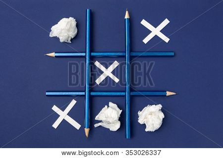 Tic Tac Toe Is Made Of Pencils And Paper. Blue Pencils On A Blue Background. Crosses From Paper, Toe