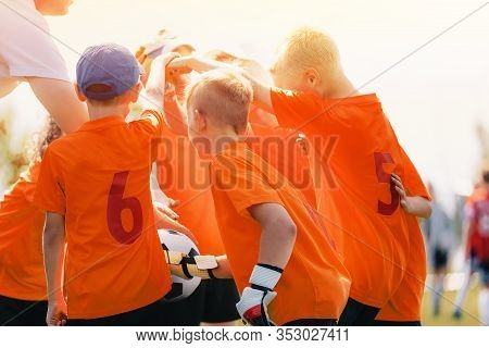 Kids In Sports Soccer Team With Coach. Junior Football Team Stacking Hands Before A School Tournamen