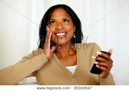 Black Woman Holding Mobile Phone And Looking Up