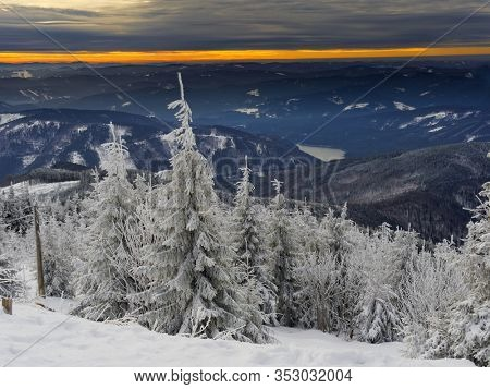 View from the top of Lysa Hora in the Czech Republic on the snowy mountains. In the foreground, trees white with snow. In the background an orange strip illuminated by the setting sun.
