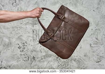Mans Hand Is Holding Leather Craft Bag On A Gray Concrete Background